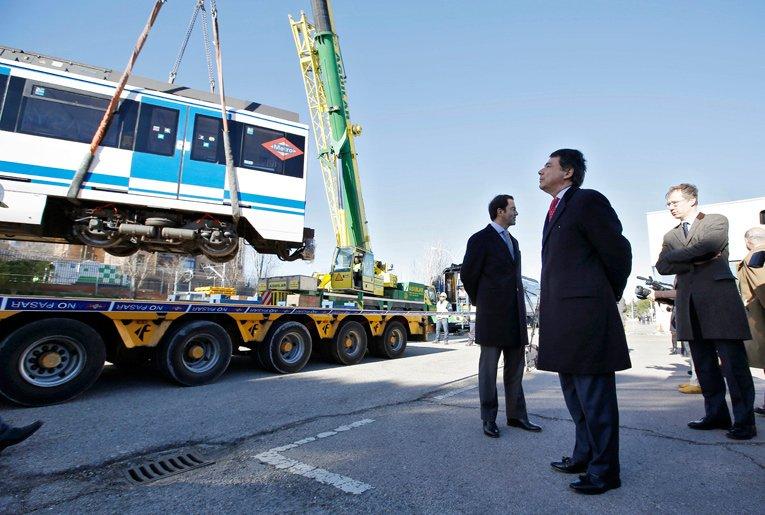 El presidente de la Comunidad de Madrid, Ignacio González, observa cómo suben al camión el primero de los trenes de la serie 6000 que parte a Buenos Aires. Foto © Metro de Madrid.